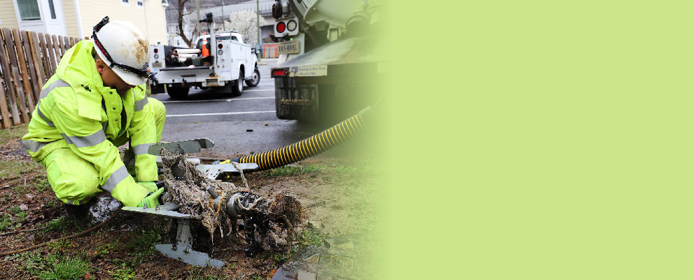 Image of Service Authority Employee Cleaning Wipes From Pipes.